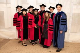 Students in convovation tent with professor