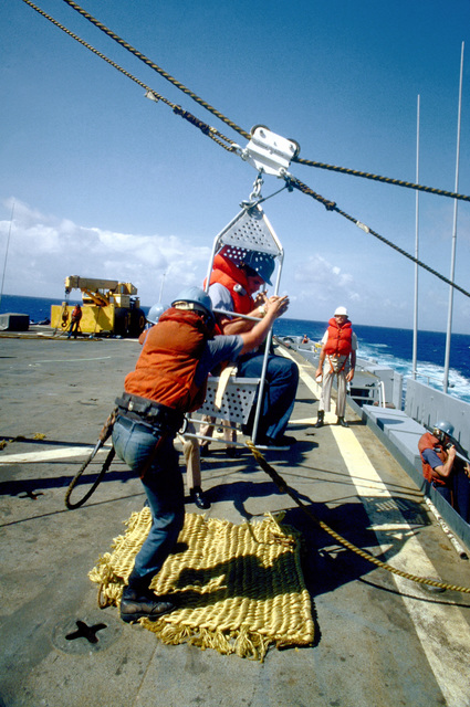 A boatswains chair is pulled to the deck of the destroyer