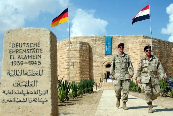 https://i0.wp.com/cdn10.picryl.com/photo/2001/10/19/two-usa-soldiers-walk-near-the-entrance-of-the-german-cemetery-at-el-alamein-b1dd65-1600.jpg?resize=696%2C467&ssl=1