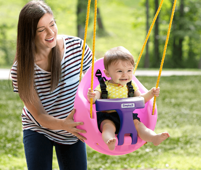 Simplay Pink Snuggle Swing Attached To Swing Set With Mother Pushing Child