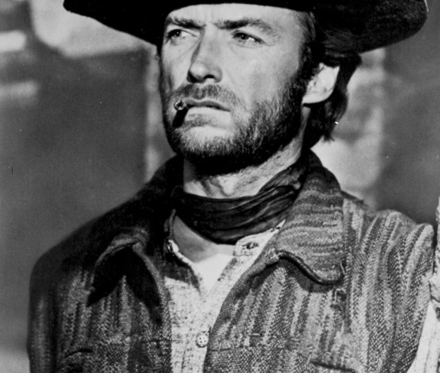 Clint Eastwood Looking Away In Cowboy Attire With Cigarette In His