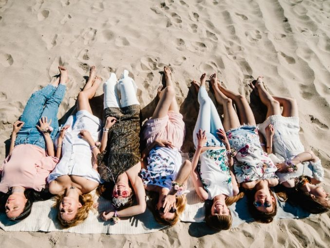 Imagen ilustrativa de un grupo de mujeres en la playa tendidas en la arena.