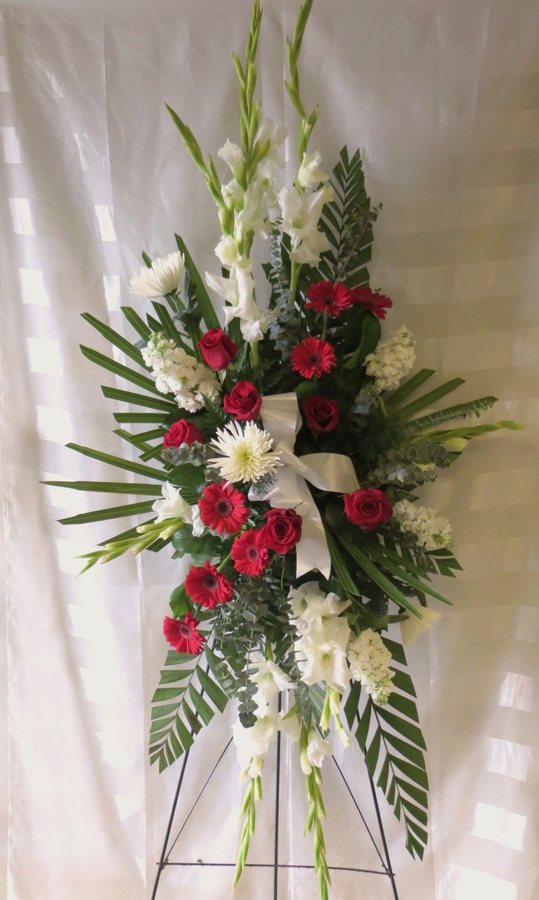 Red and white funeral flowers on a stand for delivery in