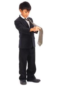 Young Boy In Suit Doing His Tie To Look Smart