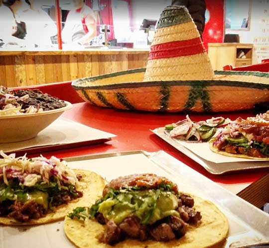 Tacos al pastor on a table and a charro hat