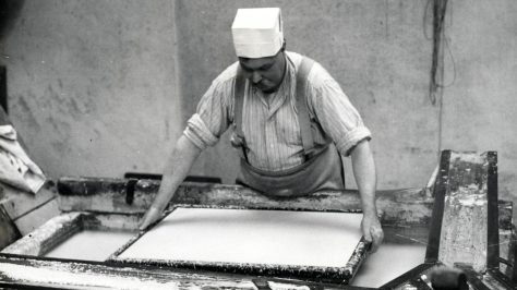 A vat man making paper in the mid-20th century.