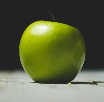 A green apple on a wooden surface with a dark background