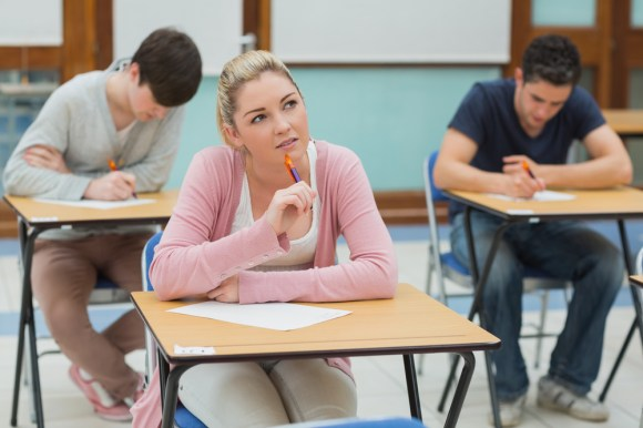 Three students sitting at desks in a classroom while writing and thinking