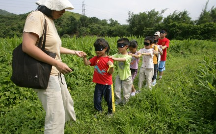 Students are taken on a blindfolded tour of the countryside near Tai Po to expose them to the sounds and smells of nature that are sadly missing in their everyday urban environment. Photo: Ricky Chung