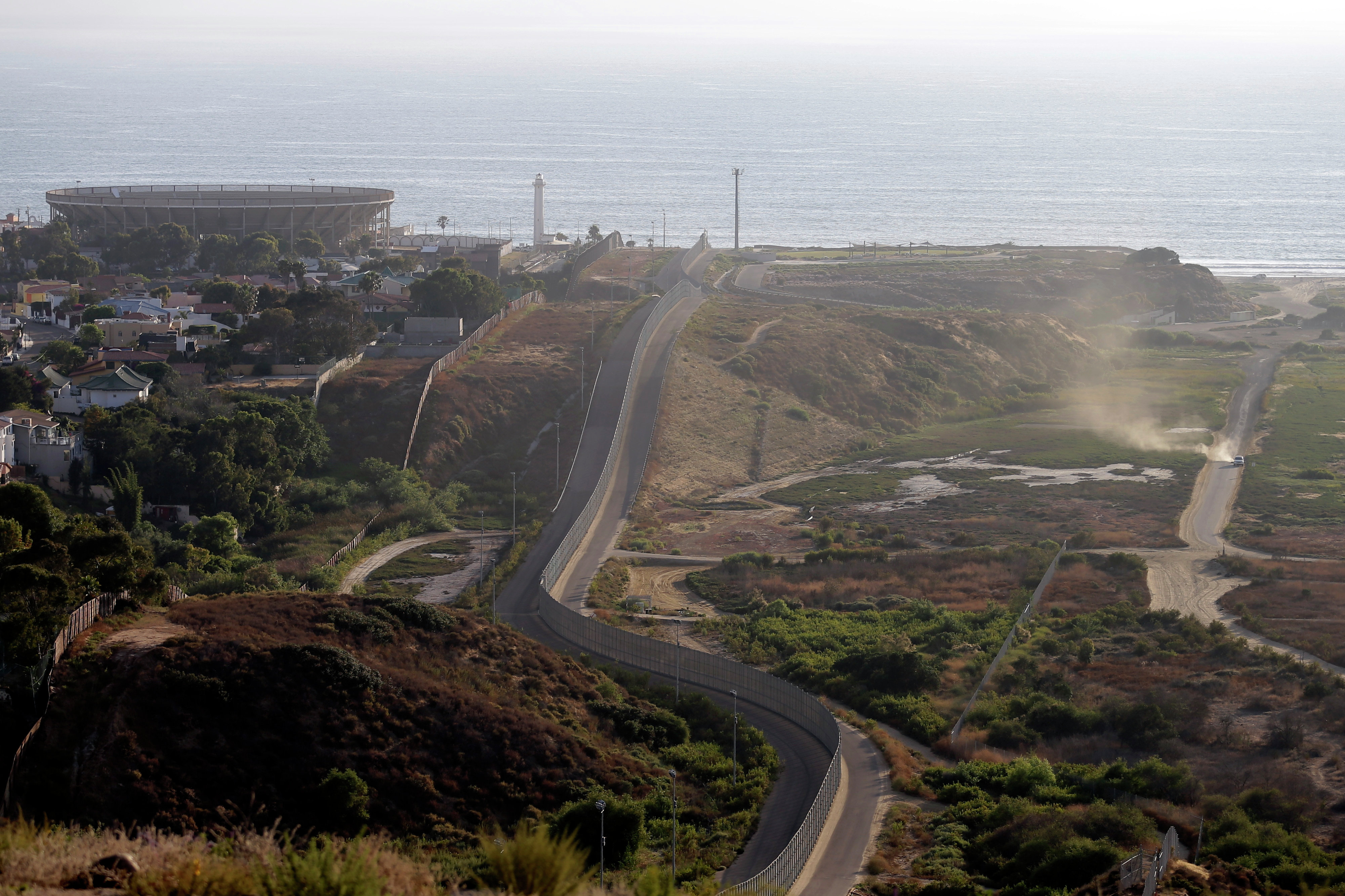 A U.S. Border Patrol vehicle, right, drives along a road running alongside the border structures that separate Tijuana, Mexico, left, from San Diego Thursday, June 13, 2013, in San Diego