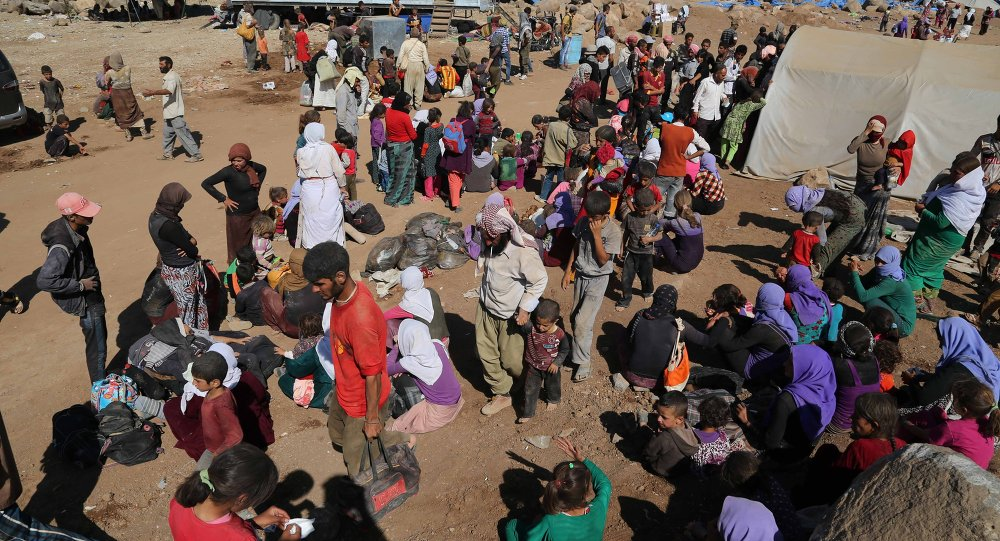 Displaced Iraqis from the Yazidi community arrive at Nowruz camp, in Derike, Syria, Tuesday, Aug. 12, 2014