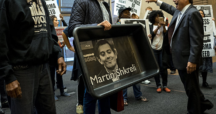 Carrying an image of Turing Pharmaceuticals CEO Martin Shkreli in a makeshift cat litter pan, AIDS activists and others are asked to leave the lobby of 1177 6th Ave. in New York, Thursday, Oct. 1, 2015, during a protest highlighting pharmaceutical drug pricing.