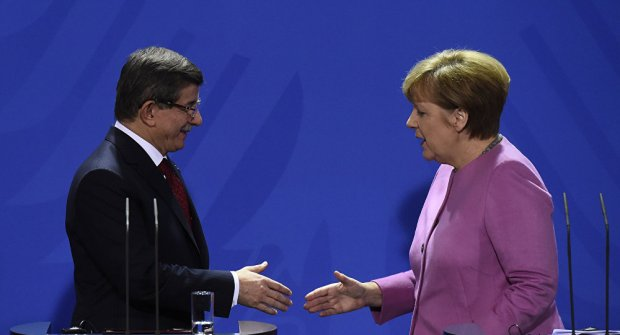 German Chancellor Angela Merkel (R) and Turkish Prime Minister Ahmet Davutoglu (L) shake hands during the press conference, after a meeting at the Chancellery, in Berlin on January 22, 2016