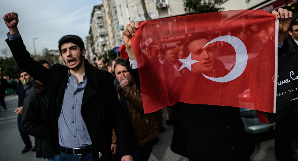 A protester holds a Turkish flag during a demonstration near the headquarters of the newspaper Zaman in Istanbul on March 6, 2016.