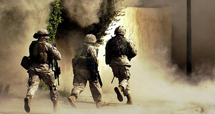 US Marines from the 2nd Battalion, 5th Marine Regiment, run to a building after detonating explosives to open a gate during a mission in Ramadi in Anbar province, Iraq