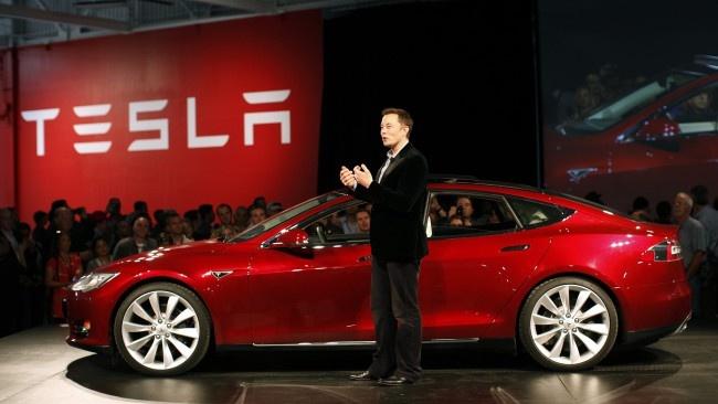 Elon Musk junto a coche Tesla