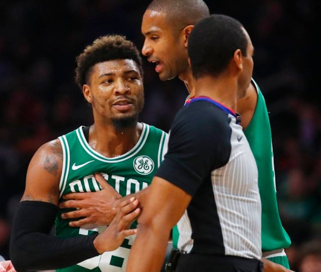 Boston Celtics Guard Marcus Smart  Is Restrained By Center Al Horford During The