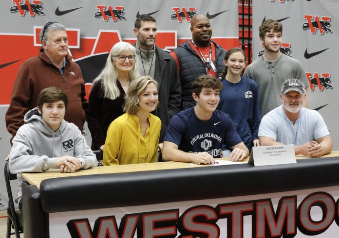 Photo - Jacob Clark poses with his family after signing a letter during Signing Day event at Westmoore High School on Wednesday, Feb. 6, 2019.  Photo by Jim Beckel, The Oklahoman.