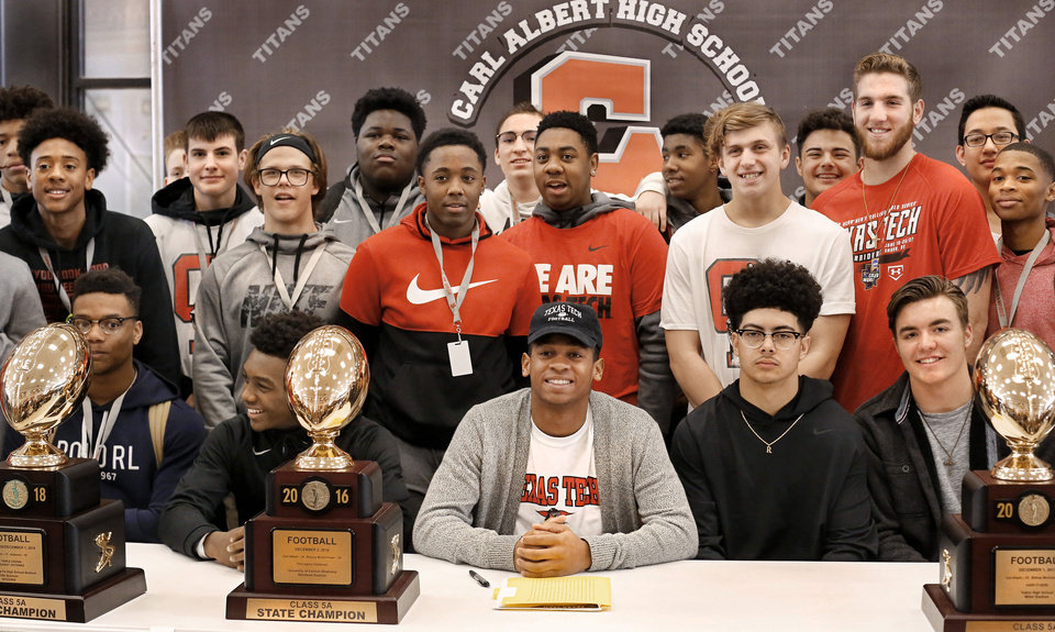 Photo - Titans football standout Dadrion Taylor, seated center, smiles while posing with football teammates after he signed letter to play football with Texas Tech University during Signing Day ceremony at Carl Albert  High School on Wednesday, Feb. 6, 2019.  Photo by Jim Beckel, The Oklahoman.