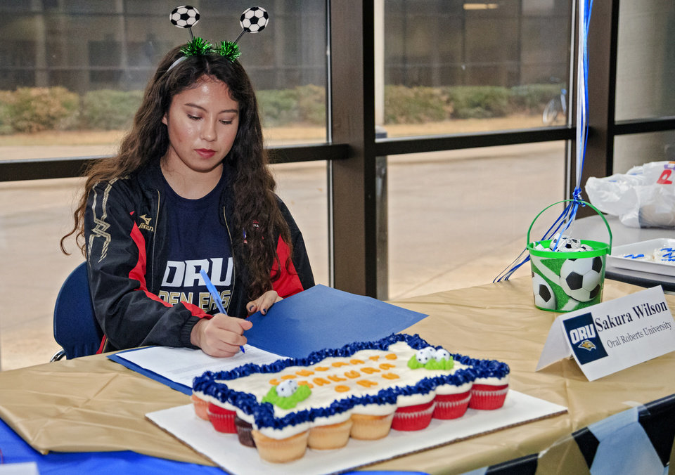 Photo - Edmond North's Sakura Wilson signs her letter of intent to play soccer for Oral Roberts University during a national signing day ceremony at the school in Edmond, Okla. on Wednesday, Feb. 6, 2019.  Photo by Chris Landsberger, The Oklahoman