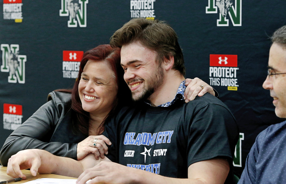 Photo - Shawn Yohn hugs her son, Blake, after watching him sign a letter for track and for cheer at Oklahoma City University during Signing Day event at Norman North High School on Wednesday, Feb. 6, 2019.  At right is Blake's, dad, Chris. Photo by Jim Beckel, The Oklahoman.