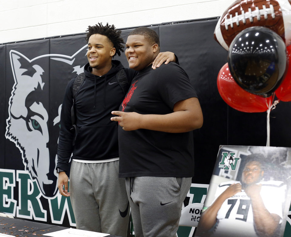 Photo - Senior Ja'Vion Combs, right, smiles while posing for a photo with fellow athlete Josh Crutchfield  as Combs greeted friends and classmates before signing a letter to play football with Northwestern Oklahoma State University during Signing Day event at Norman North High School on Wednesday, Feb. 6, 2019.  Photo by Jim Beckel, The Oklahoman.