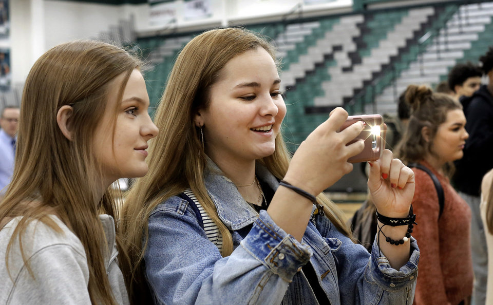 Photo - Two students take pictures of their athlete classmates as they sign letters during Signing Day at Norman North High School on Wednesday, Feb. 6, 2019.  Photo by Jim Beckel, The Oklahoman.