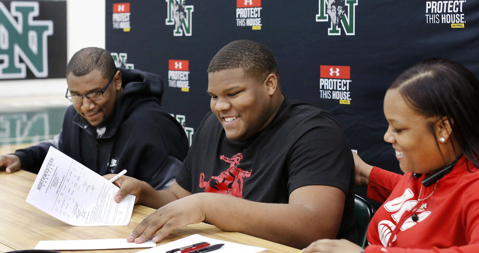 Photo - Seated between his parents, senior Ja'Vion Combs grins after signing his name to a letter to play football with Northwestern Oklahoma State University during Signing Day event at Norman North High School on Wednesday, Feb. 6, 2019.  Photo by Jim Beckel, The Oklahoman.