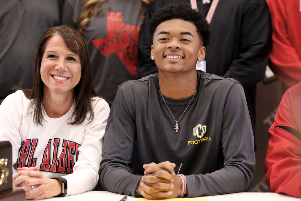 Photo - Titans senior Anthony Davis smiles as he sits with teammates for a group photo after he signed letter to play at UCO during Signing Day ceremony at Carl Albert  High School on Wednesday, Feb. 6, 2019.  At left is Kimberly Davis, Carl Albert High School's athletic trainer. Photo by Jim Beckel, The Oklahoman.