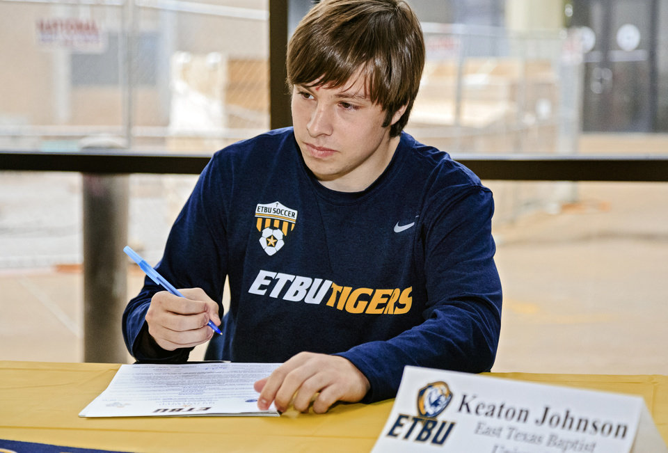 Photo - Edmond North's Keaton Johnson prepares to sign his letter of intent to play soccer for East Texas Baptist University during a national signing day ceremony at the school in Edmond, Okla. on Wednesday, Feb. 6, 2019.  Photo by Chris Landsberger, The Oklahoman