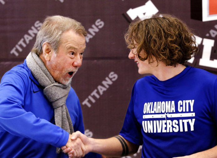 Photo - Head soccer coach Brian Harvey enthusiastically congratulates senior Thomas Mcelya after he signed letter to play soccer on Harvey's team at Oklahoma City University during Signing Day ceremony at Carl Albert  High School on Wednesday, Feb. 6, 2019.  Photo by Jim Beckel, The Oklahoman.