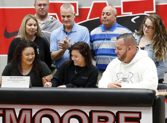 Photo - Nevaeh Daniel signs letter to play at Southwestern Christian College during Signing Day event at Westmoore High School on Wednesday, Feb. 6, 2019.  Photo by Jim Beckel, The Oklahoman.
