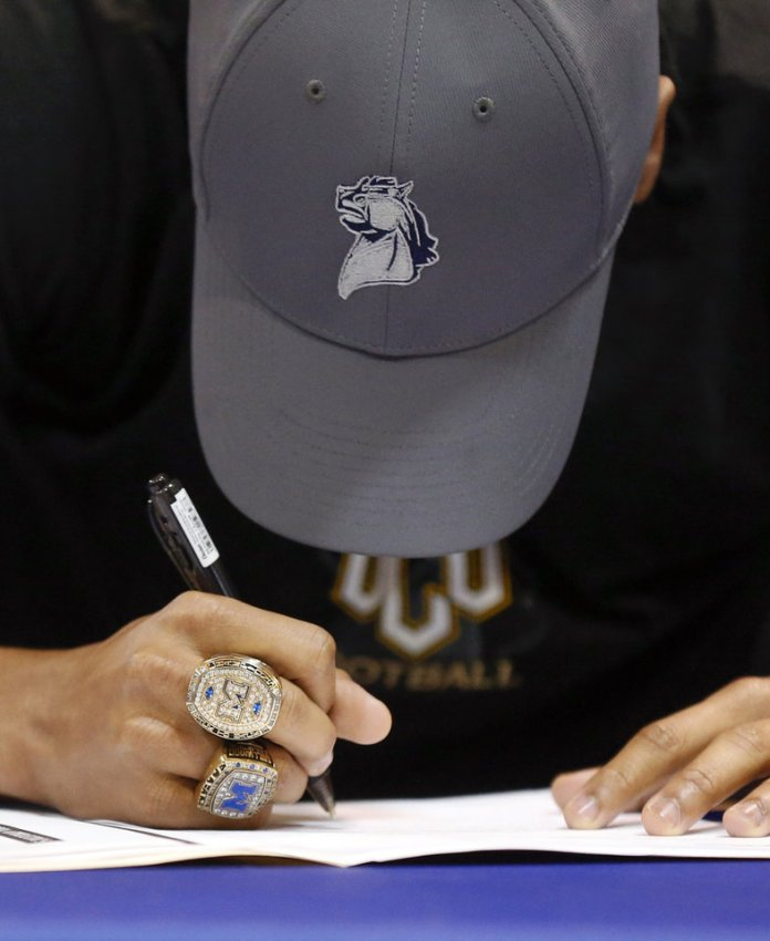 Photo - Millwood's Dontez Fagan wears his two state championship rings as he signs to play at UCO during the signing ceremony for high school football players in the Millwood Field House in Oklahoma City, Wednesday, Feb. 6, 2019. Photo by Nate Billings, The Oklahoman