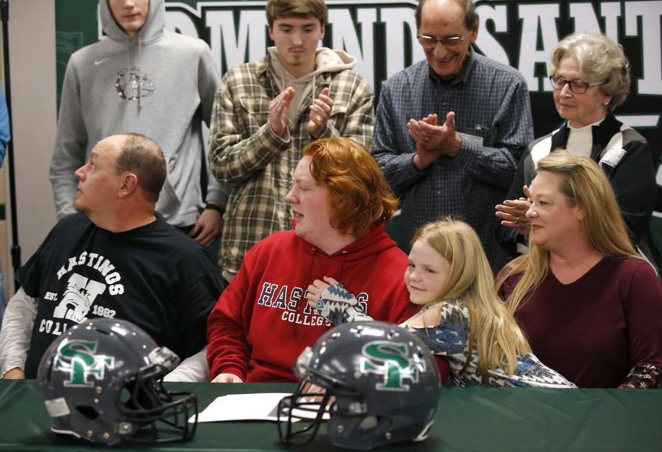 Photo - Kincade White waits signs to play football at Hastings as he surrounded by his family as during signing day ceremony at Edmond Santa Fe High School in Edmond, Okla., Wednesday, Feb. 6, 2019. His dad Tim White, Kacey and sister Makenna  are seated next to him. Photo by Sarah Phipps, The Oklahoman