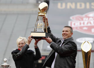 Ohio State coach Urban Meyer, right, and The Associated Press' east regional director Eva Parziale hold up The Associated Press college football national championship trophy during a celebration of the Buckeye's 2014 College Football Playoff national champion at Ohio Stadium in Columbus, Ohio, Saturday, Jan. 24, 2015. (AP Photo/Paul Vernon)