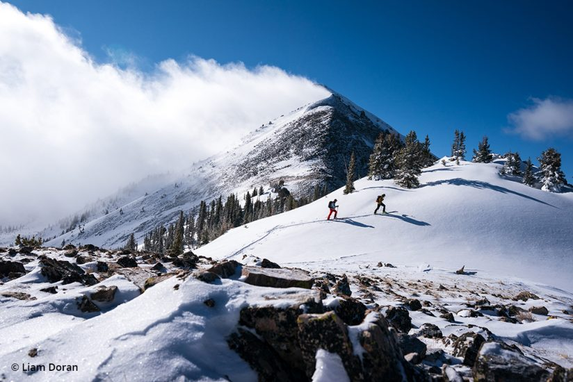 Two skiers make their way in the backcountry.