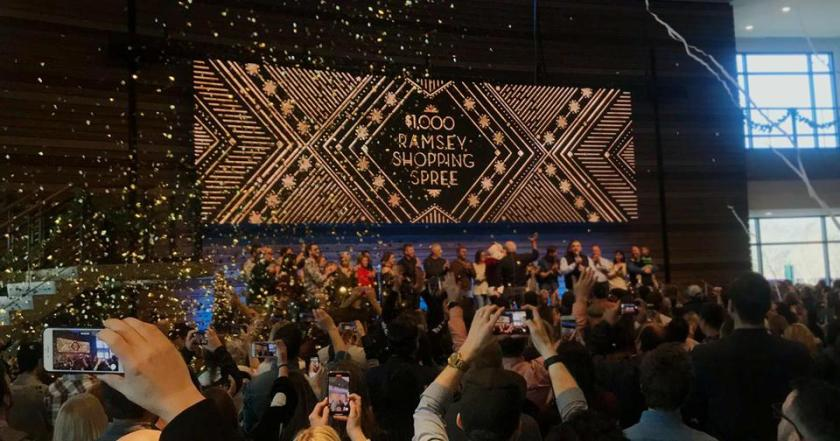 Confetti falling on 900 Ramsey Solutions team members as they learn that Dave has given them each $1000 for Christmas.
