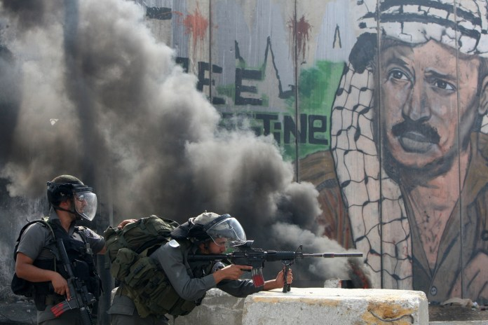 Retrato de Arafat al fondo de dos soldados de las Fuerzas de Defensa de Israel