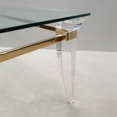 vintage coffee table with a gold plated frame assymetrical lucite table legs 1980s