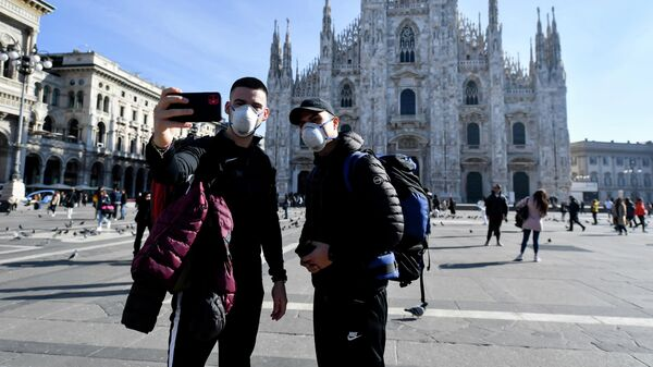 Tourists are photographed against the backdrop of the Cathedral in Milan
