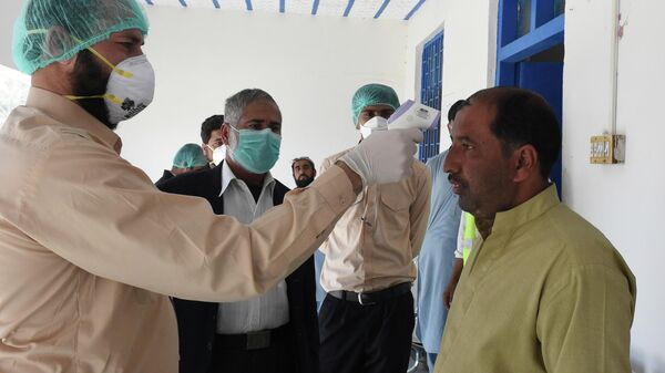 A doctor checks the body temperature of a man returning from Iran to a quarantine zone in the Pakistani-Iranian border town of Taftan