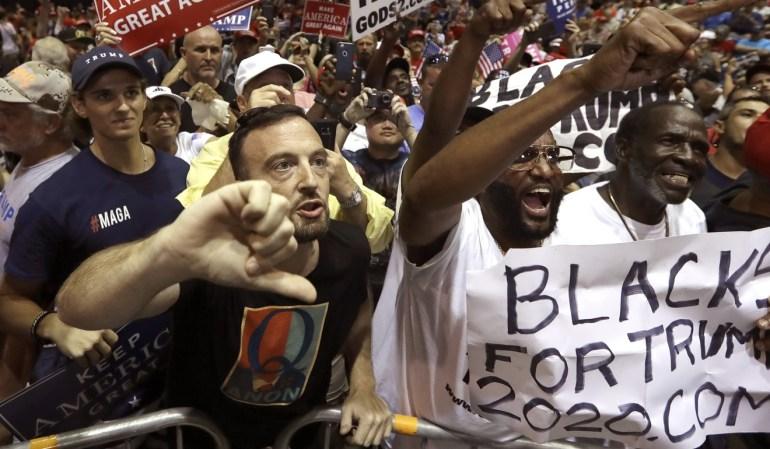"""Los partidarios del presidente Donald Trump gritan a un equipo de noticias de CNN antes de un mitin en Tampa, Florida, el martes.  El hombre de la izquierda lleva un logotipo de """"Q"""" en su camisa.  Foto AP"""