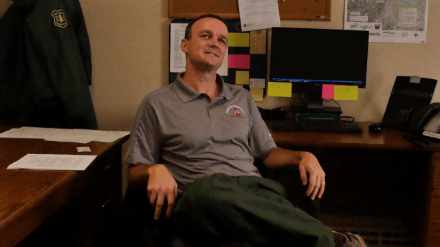 Jason Brey, park ranger, sitting in his chair in his office.