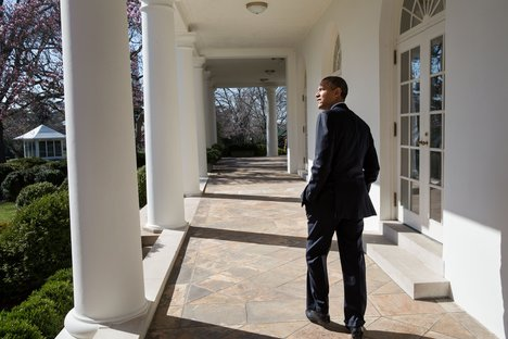 File - President Barack Obama looks out over the Rose Garden as he walks along the Colonnade of the White House, April 2, 2013.