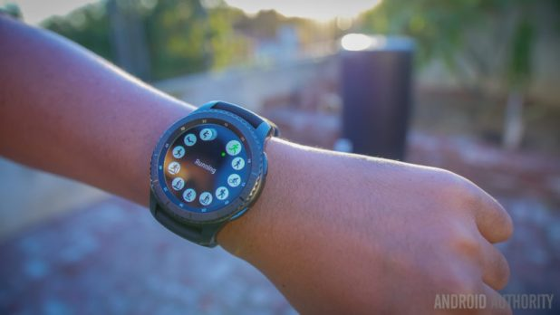 The Samsung Gear S3 smartwatch on a wrist in a park at sunset.