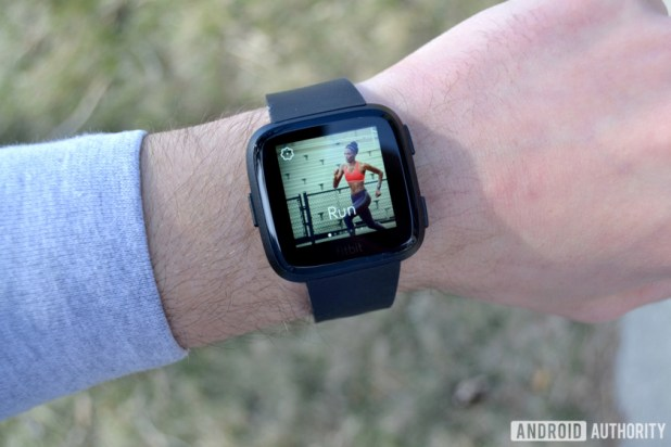 fitbit versa smartwatch on wrist showing running screen connected gps