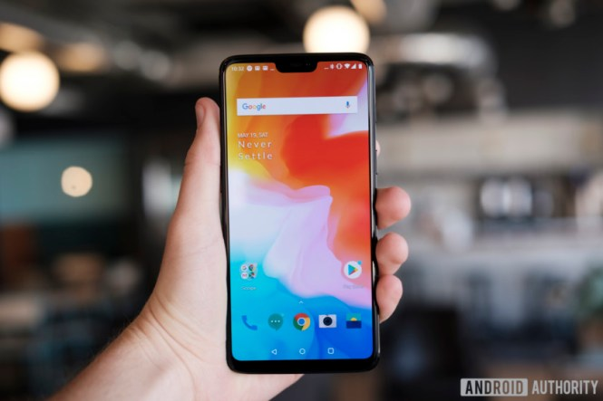 An image of the OnePlus 6 held out in a person's left hand with the screen on.
