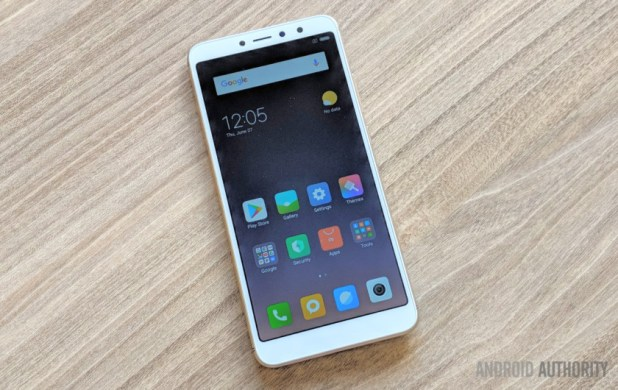 Xiaomi Redim Y2 smartphone in white, face-up on a wooden desk.