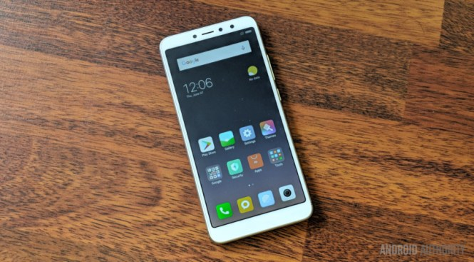 Xiaomi Redim Y2 smartphone in white, on a wooden table, face-up.