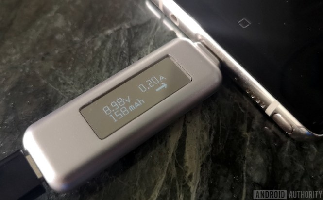 A charging dongle shows the amount of current passing to a fully charged smartphone